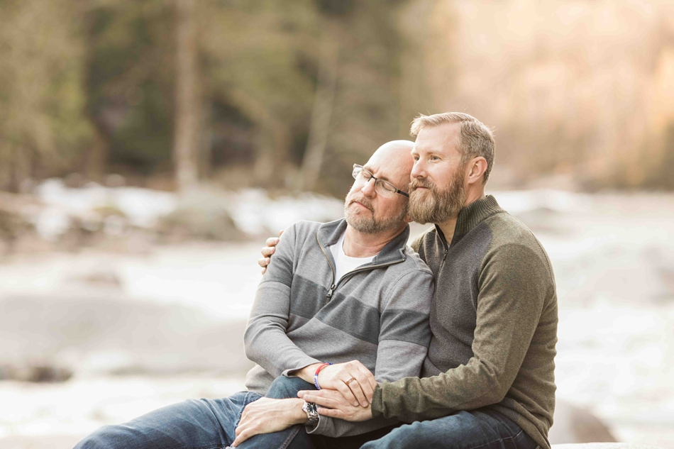 Picture of an engaged couple sitting by a river during their spring outdoor mountain engagement shoot in Snohomish, near Seattle, WA. | Joanna Monger Photography | Snohomish Wedding Photographer