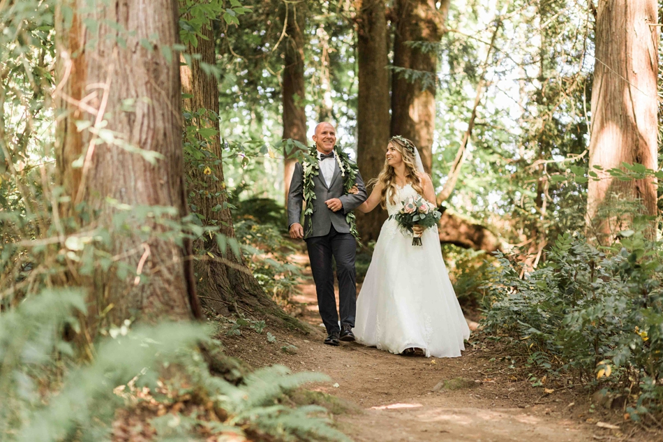 The bride walks hand in hand at Twin Willow Gardens in Snohomish. Photographs by Joanna Monger Photography, Award Winning Snohomish Wedding Photographer.
