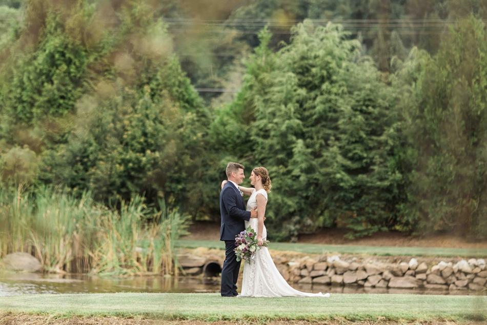 Bride puts arm around groom at Pine Creek Nursery in Monroe. Photographs by Joanna Monger Photography, Snohomish's Best Wedding Photographer.