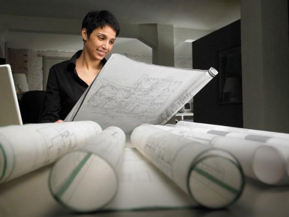 Female architect reading blueprint at desk