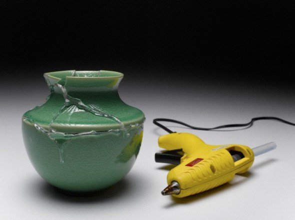 Broken green vase glued together beside yellow glue gun