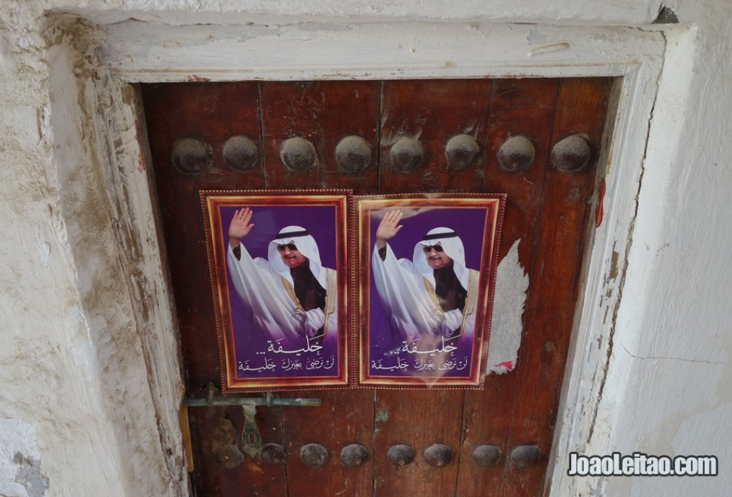 Posters colados numa porta de madeira no bairro histórico da ilha de Murharraq no Barém