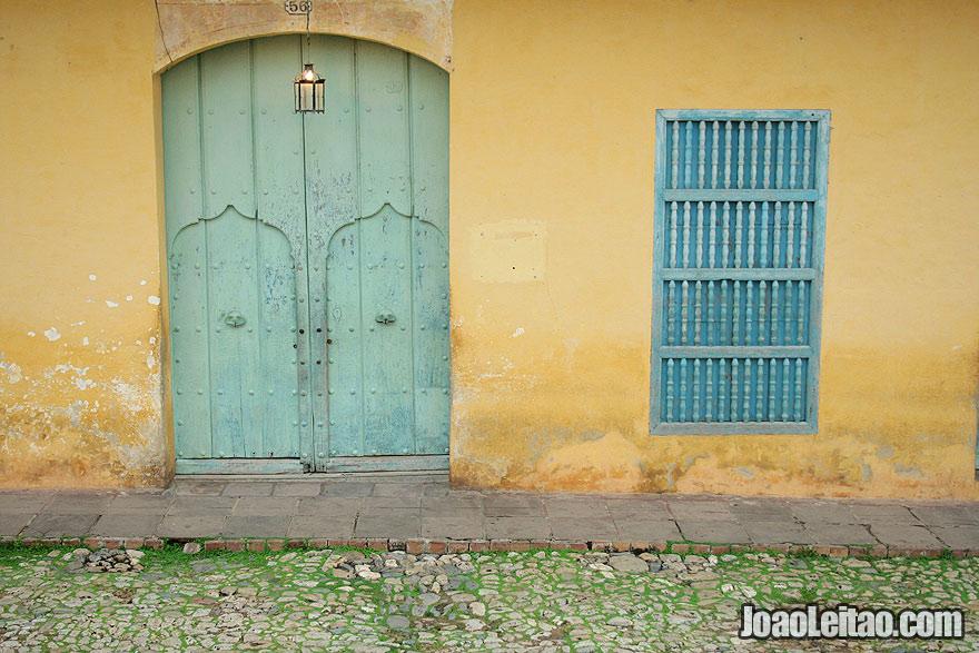 Wooden green door and blue window with yellow buildin in Trinidad