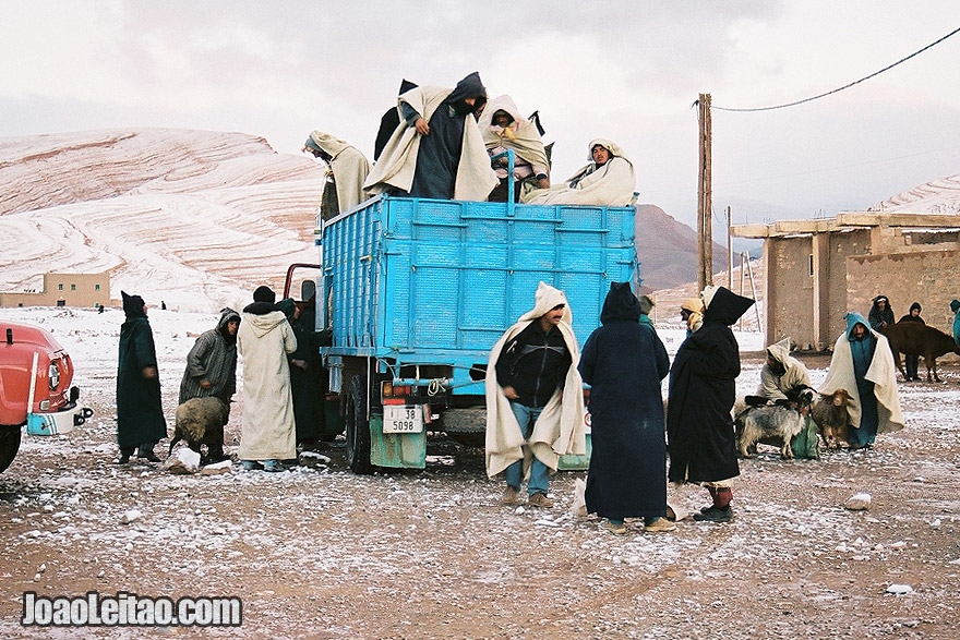 Photo of men descending from truck for the Ait Hani morning market, Morocco