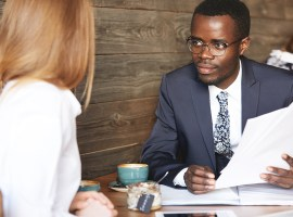 Recruiting and human resource concept. African businessman interviewing Caucasian female candidate for a secretary position looking and listening to her attentively while sitting at a coffee shop