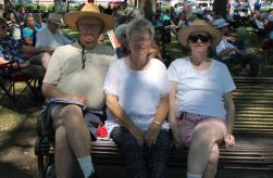 From left to right, James Jernigan, Louise Bradford and Janice Spruill grab a shady spot in the Singing Grove to enjoy the gospel music.