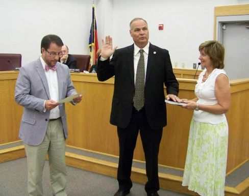Smithfield town manager Michael Scott (center) takes his Oath of Office from Mayor Andy Moore (left) as Scott's wife, Peggy, holds a Bible. JoCoReport.com Photo