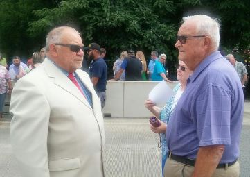 Retired Deputy Sheriff Jimmy Doan (right) meets Johnston County Commissioner Chairman Tony Braswell at Friday's ceremony. Doan worked with Deputy West on the Johnston County Sheriff's Office.