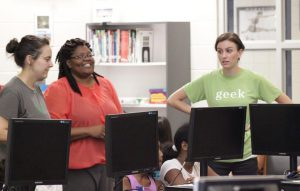 Cari DelMariani (right), Director of Programs for Kramden Institute, works with Selma Middle School Teacher of the Year Tarsha Johnson (center) and Kramden Institute office manager Kristina Zuidema (left) to train students on how to use their new computers.