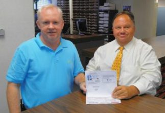 """(Left to right) Johnston County Veterans Services Director Robert Boyette and Johnston County Register of Deeds Craig Olive display a """"Thank a Vet"""" Photo ID card that is being distributed to area veterans to receive discounts at participating businesses. The discount program will launch November 1st."""
