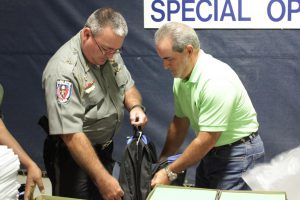 Fraternal Order of Police Lodge #88 President Ronald Daniels (left) helps Johnston County Board of Education member Keith Branch (right) pack book bags for students.