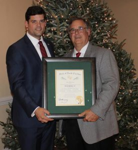 (Left to right) DeVan Barbour, IV presents his father, retiring Johnston County Commissioner DeVan Barbour, III the Order of the Long Leaf Pine during a private retirement reception at the County Club of Johnston County Thursday night.