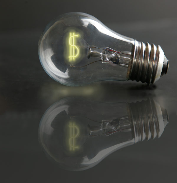 light bulb with money sign filament laying on a reflective surface