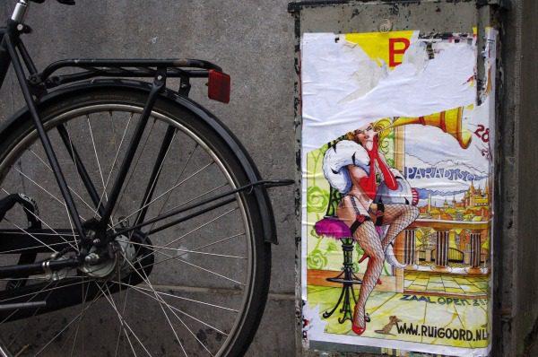 Bike wheel beside art
