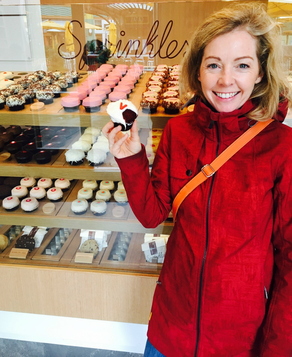 woman eating Sprinkles cupcake