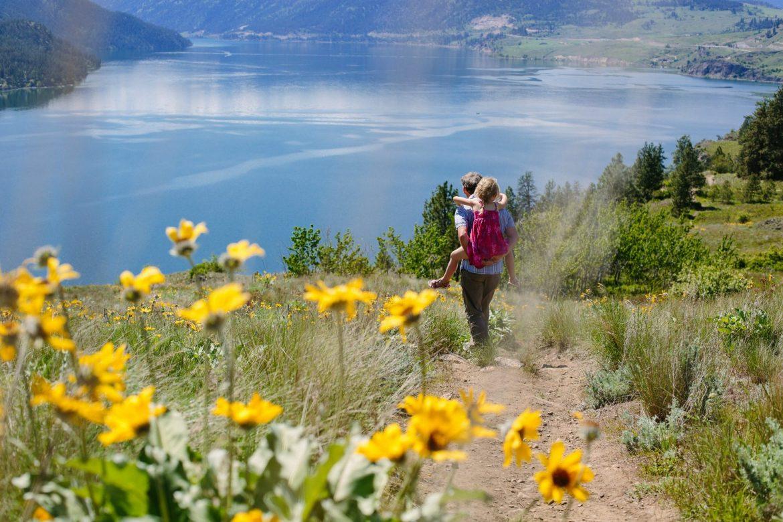 family hiking around shores of lake