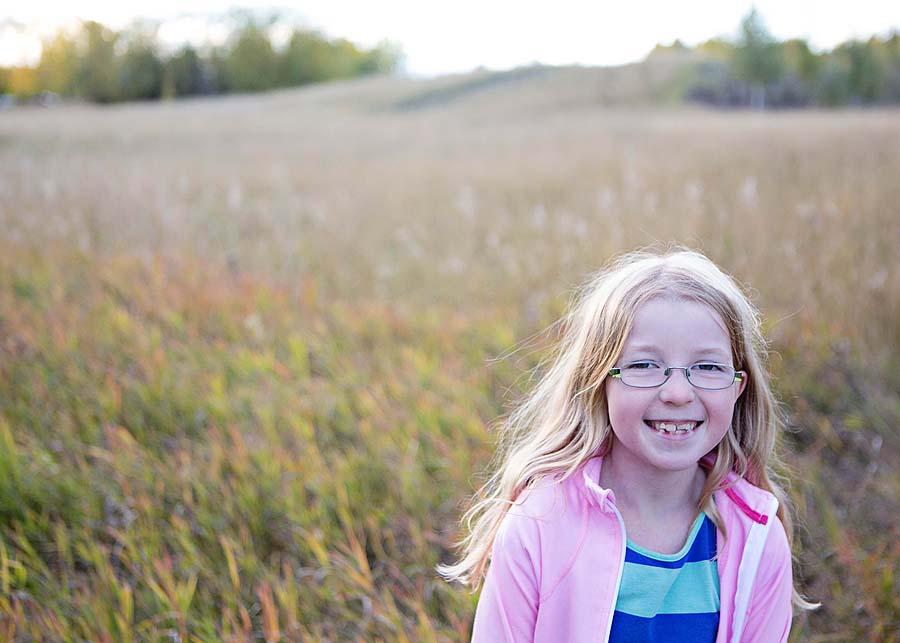 girl in a field wearing glasses