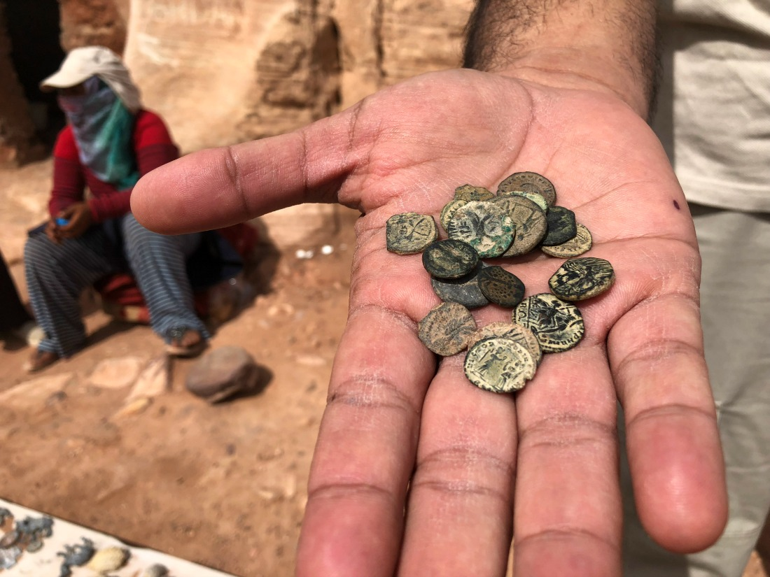 man holding ancient coins