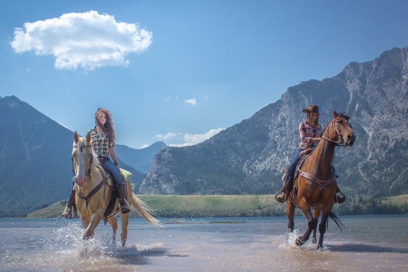 women riding horses in the mountains