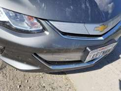 Damage to front bumper, grill, and hood on the passenger side of the license plate.