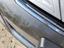 Damage to front bumper on the passenger side of the license plate.