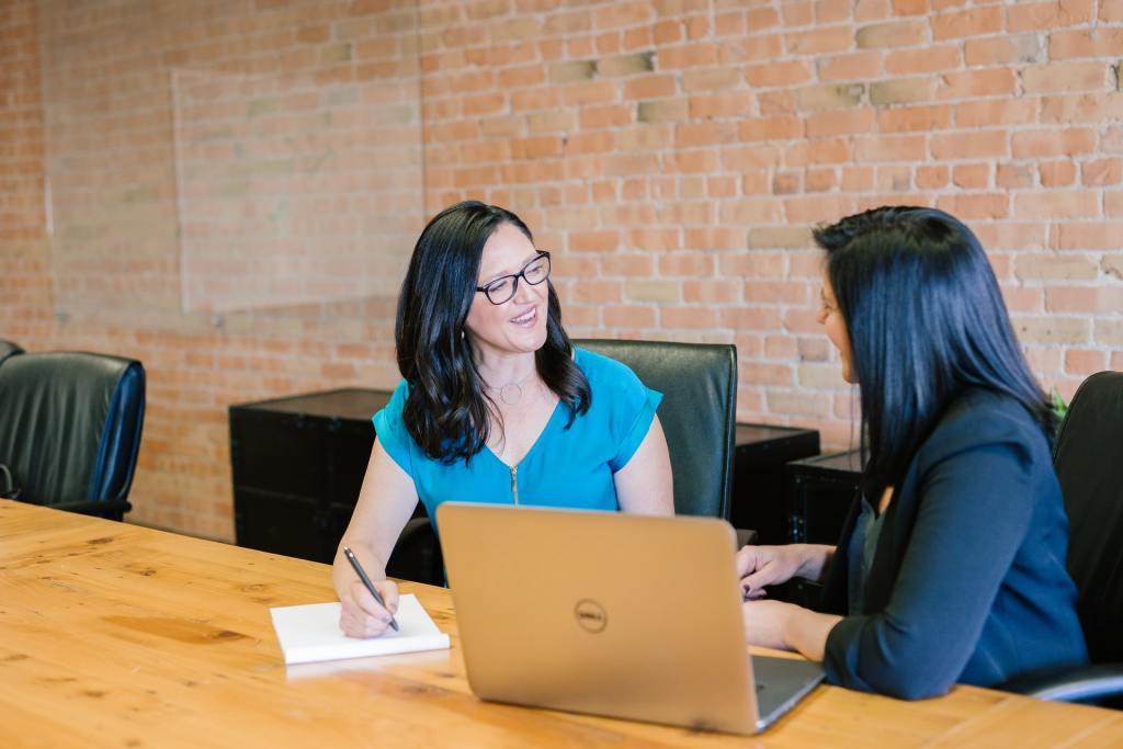 Woman in t-shirt sitting beside woman in suit jacket
