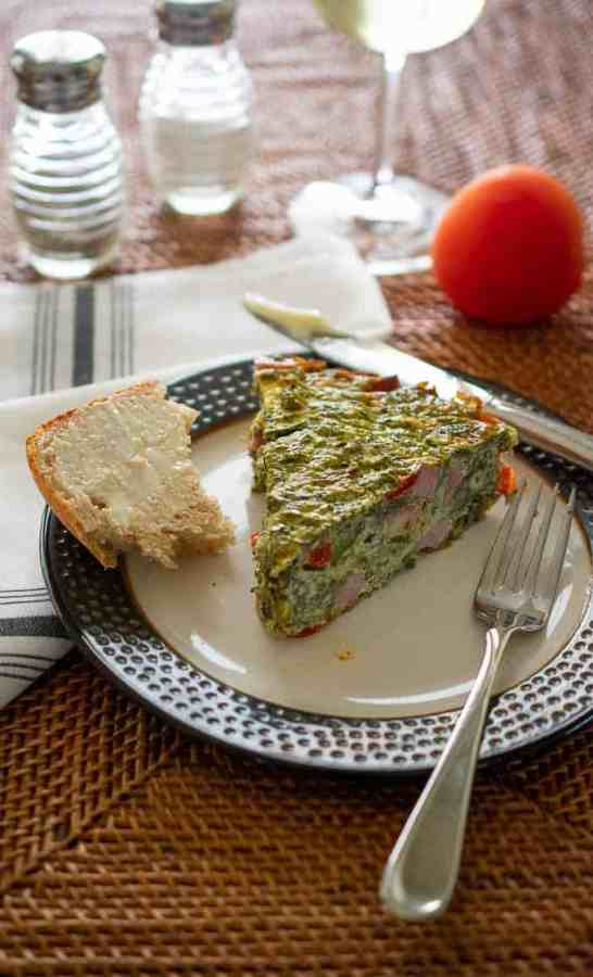 Plate with a slice of vegetable quiche and buttered bread.