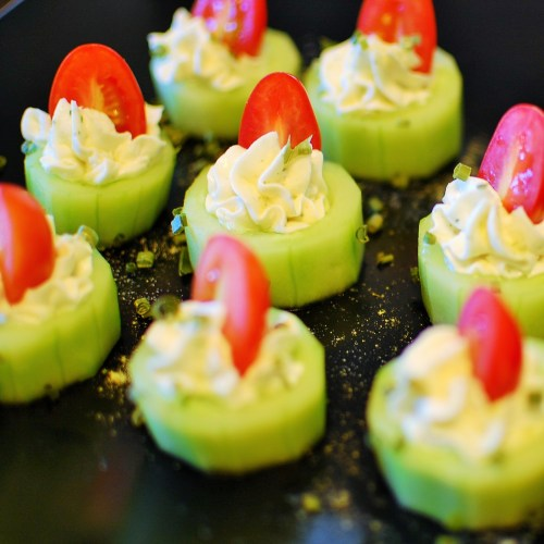 Stuffed cucumber bites, sliced cucumbers with piped on cream cheese and halved grape tomato