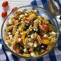 Overhead view of cold pasta salad in a glass bowl