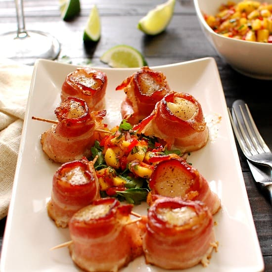 Bacon wrapped scallops with mango salsa. Delicious appetizer or as a main course. The sweet seafood flavor of the scallops blends nicely with the salty meatiness of the bacon. This is a yummy recipe! | joeshealthymeals.com