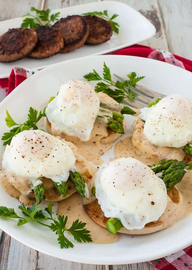 Poached eggs on a toasted English muffin with asparagus and white sauce.