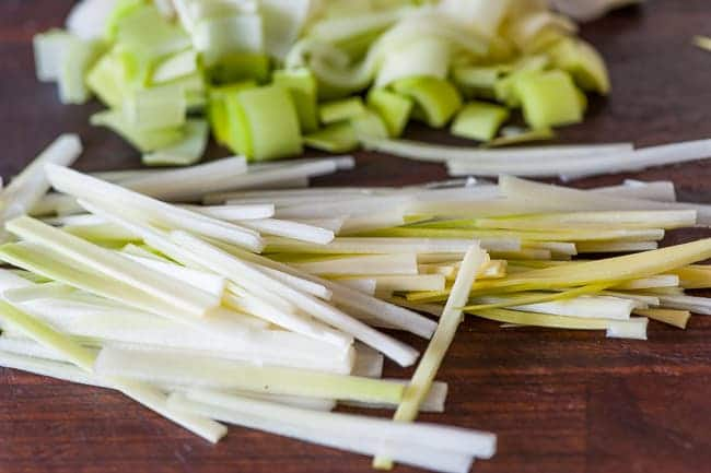 Chopping leek slivers for frying.