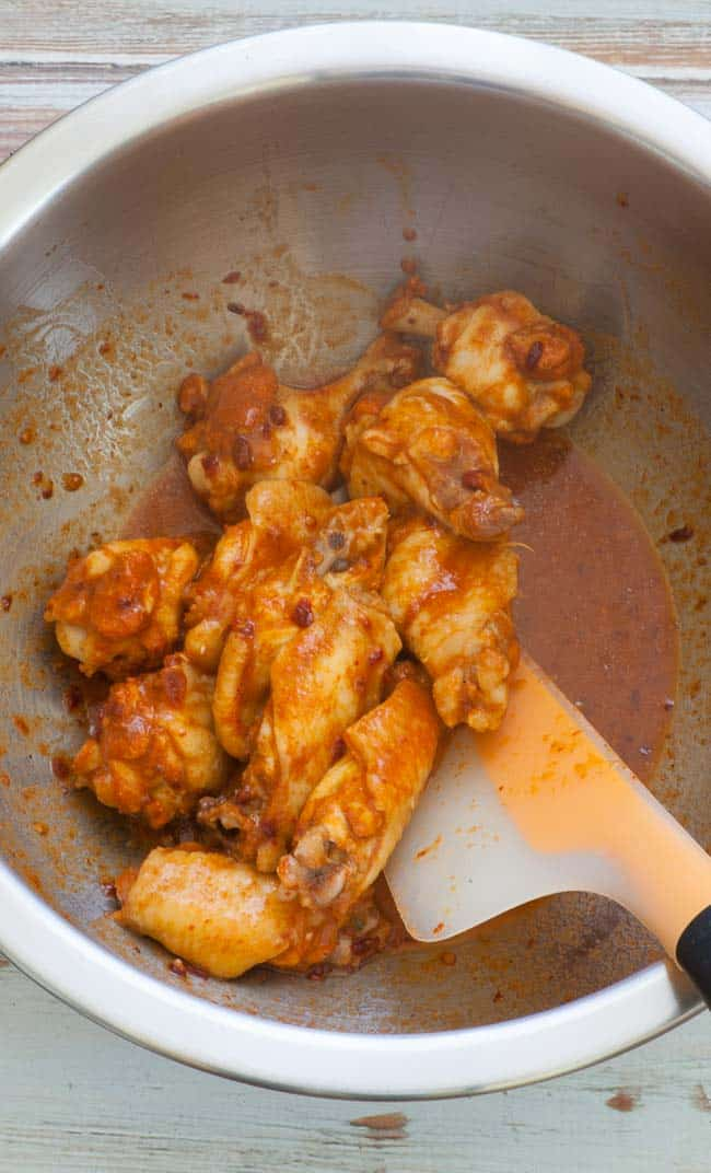 Mixing the cooked chicken wings in the spicy glazing sauce. | joeshealthymeals.com