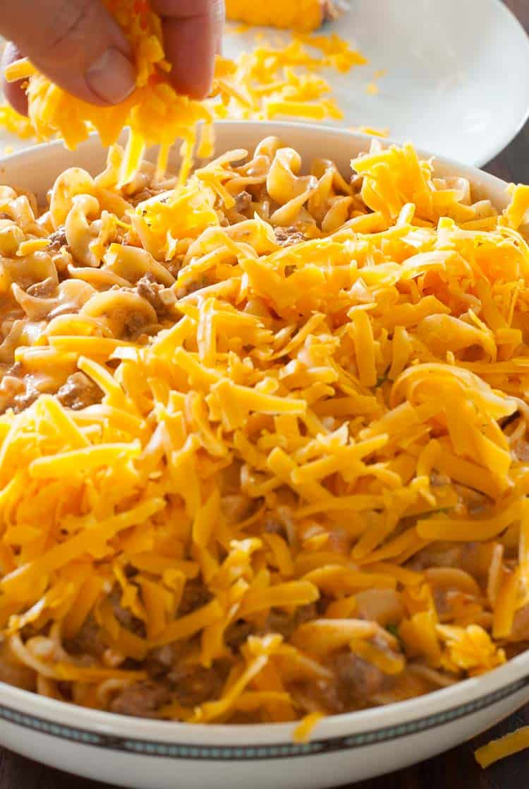 Adding grated cheddar cheese to the noodle bake. | joeshealthymeals.com