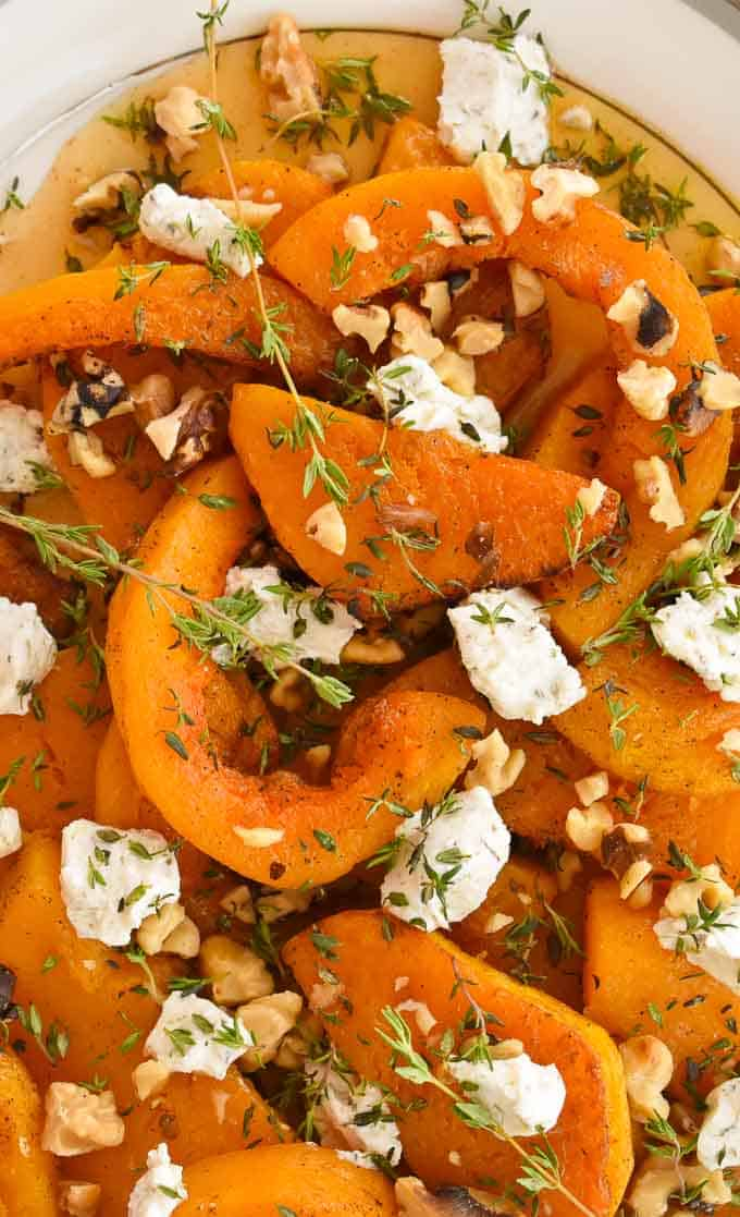 close up view of Roasted butternut squash with maple syrup, toasted walnuts and goat cheese.