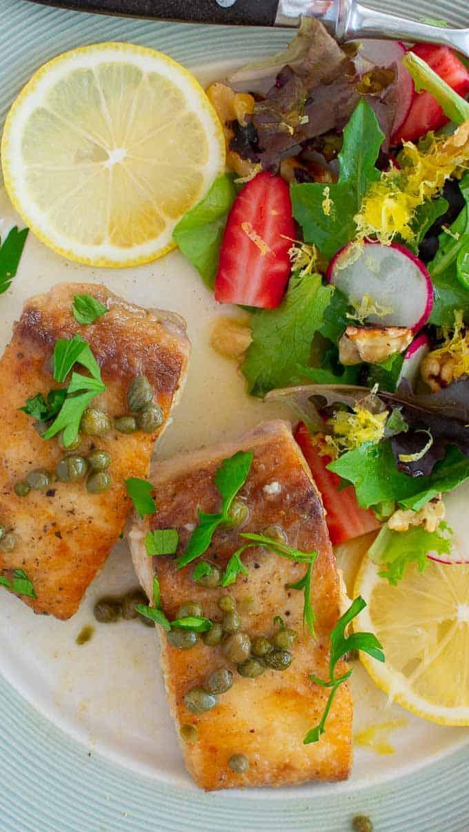 Mahi mahi fish piccata with a side salad.