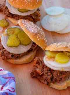 Pulled pork sandwiches with sliced onion and pickle chips.