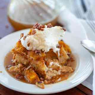A plate of pumpkin bread pudding with whipped cream.