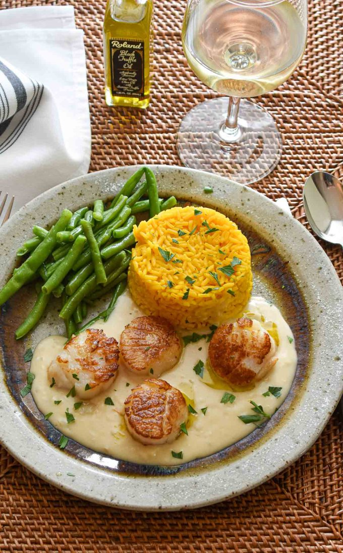 Plate of scallops and lobster sauce with rice and green beans.