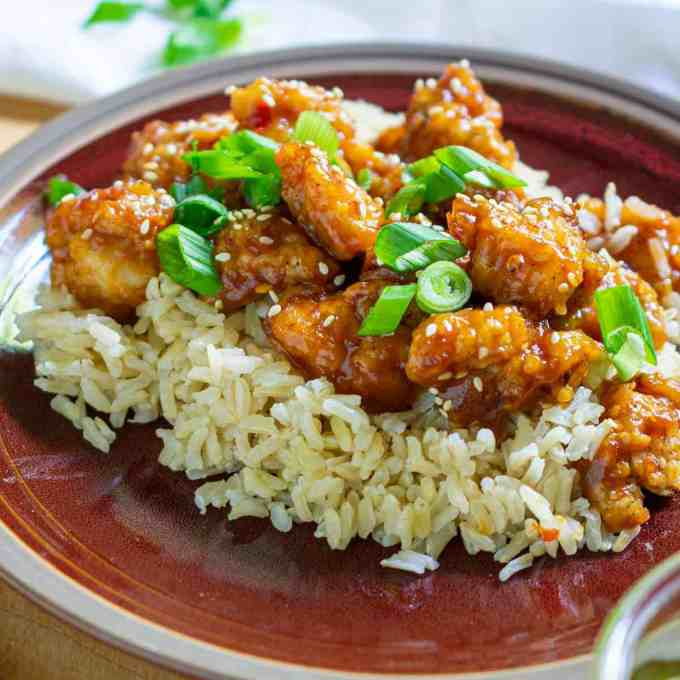 Plate of General Tso chicken on a bed of rice.