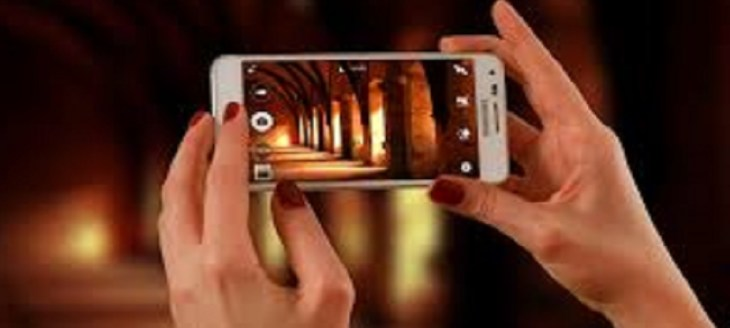 holding celphone and taking picture