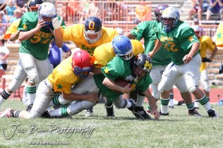 A group of East All-Stars tackle West All-Star Guy Fullmer of Dighton High School (#24) during the Kansas Eight Man Football Association Division II All-Star Game at Trojan Field in Beloit, Kansas on June 9, 2012. (Photo: Joey Bahr, www.joeybahr.com)