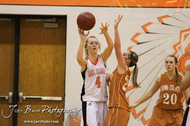 Larned Lady Indian Roxy Foster (#4) throws a pass while Kiowa County Lady Maverick Riann Heft (#22) defends during the Larned Lady Indians versus Kiowa County Lady Mavericks First Round Game with Larned winning 50 to 39 at the 6th Annual Keady Basketball Classic held at Larned Middle School in Larned, Kansas on December 3, 2012. (Photo: Joey Bahr, www.joeybahr.com)