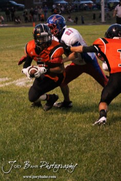 Larned Indian Jamil Shoemaker (#7) tries to evade the tackle of Ellinwood Eagle Kyle Jenks (#21) during the Ellinwood versus Larned High School football game with the Larned Indians winning 60 to 0 at Larned High School in Larned, Kansas on September 13, 2013. (Photo: Joey Bahr, www.joeybahr.com)
