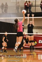 Hoisington Lady Cardinal Jordan Moore (#7) hits the ball over the net while Smoky Valley Lady Viking Hanah Godfrey (#3) tries to block it during the Hoisington versus Smoky Valley volleyball match with Hoisington winning in two sets at Hoisington Activity Center in Hoisington, Kansas on October 22, 2013. (Photo: Joey Bahr, www.joeybahr.com)