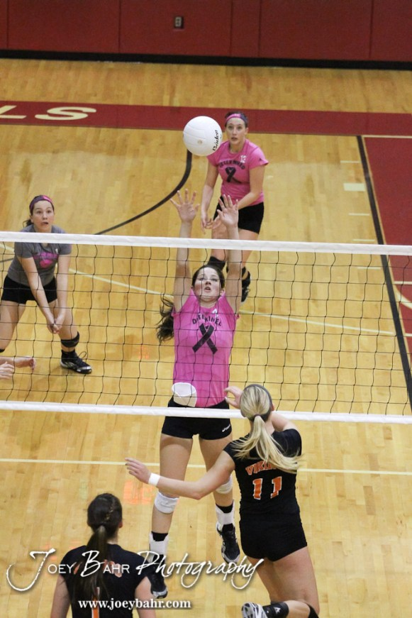 Hoisington Lady Cardinal Jordan Moore (#7) goes to block a ball from going over the net during the Hoisington versus Smoky Valley volleyball match with Hoisington winning in two sets at Hoisington Activity Center in Hoisington, Kansas on October 22, 2013. (Photo: Joey Bahr, www.joeybahr.com)