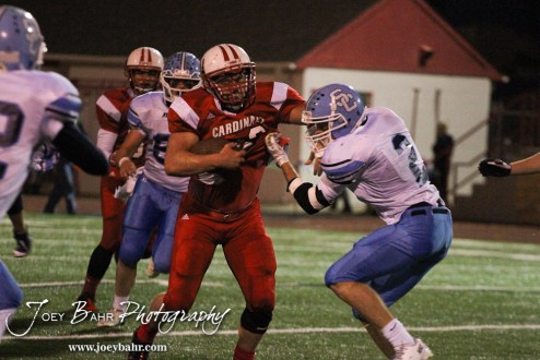 Hoisington Cardinal Avery Urban (#23) stiff arms Scott City Beaver Brayden Strine (#2) during the KSHSAA Class 4A District 15 Football game between Scott City and Hoisington with Scott City winning 14 to 0 at Elton Brown Field in Hoisington, Kansas on October 18, 2013. (Photo: Joey Bahr, www.joeybahr.com)