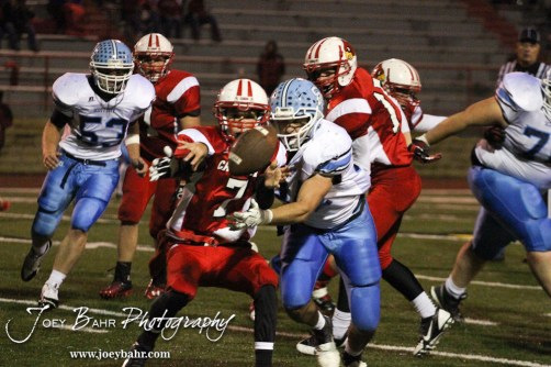 Hoisington Cardinal Taylor Richter (#7) pitches the ball while under pressure during the KSHSAA Class 4A District 15 Football game between Scott City and Hoisington with Scott City winning 14 to 0 at Elton Brown Field in Hoisington, Kansas on October 18, 2013. (Photo: Joey Bahr, www.joeybahr.com)