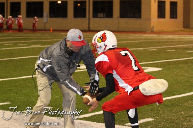 Hoisington Cardinal Head Coach Jason Ingram hikes a ball to Taylor Richter (#7) during the KSHSAA Class 4A District 15 Football game between Scott City and Hoisington with Scott City winning 14 to 0 at Elton Brown Field in Hoisington, Kansas on October 18, 2013. (Photo: Joey Bahr, www.joeybahr.com)