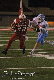 Hoisington Cardinal Nolan McCurry (#22) stiff arms Scott City Beaver Brayden Strine (#2) during the KSHSAA Class 4A District 15 Football game between Scott City and Hoisington with Scott City winning 14 to 0 at Elton Brown Field in Hoisington, Kansas on October 18, 2013. (Photo: Joey Bahr, www.joeybahr.com)